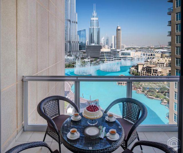 красивый вид с балкона небоскреба на башню Бурдж-Халифа и фонтаны в Дубае