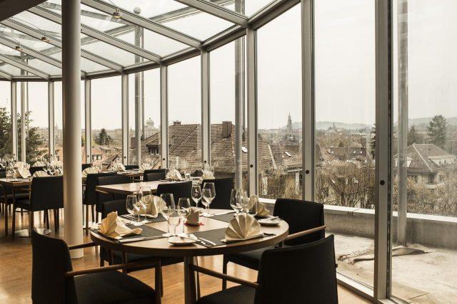 красивый вид на достопримечательности Берна через панорамное окно ресторана отеля