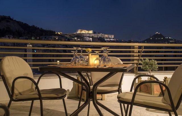 красивый вид на ночной Акрополь в Афинах с балкона отеля