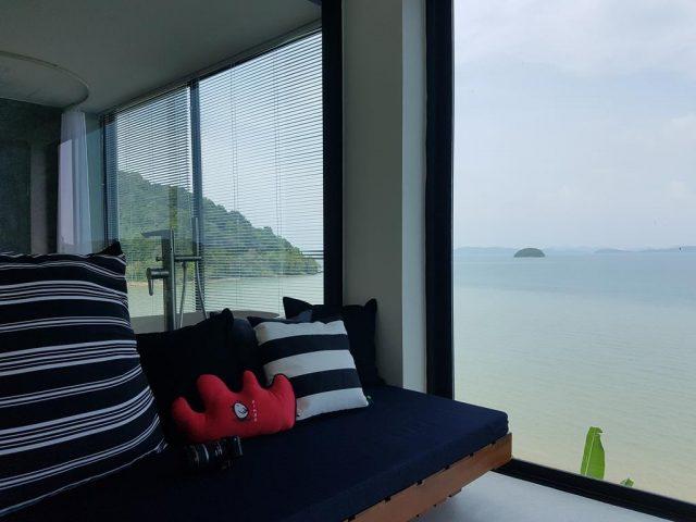 красивый вид на море через огромное окно в номере отеля на острове Пхукет