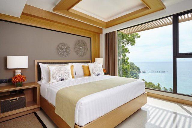 красивый вид на море через окно в пол в номере отеля на острове Пхукет
