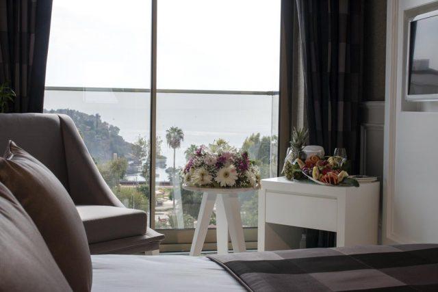 красивый вид на море и город через окно в пол в отеле Антальи