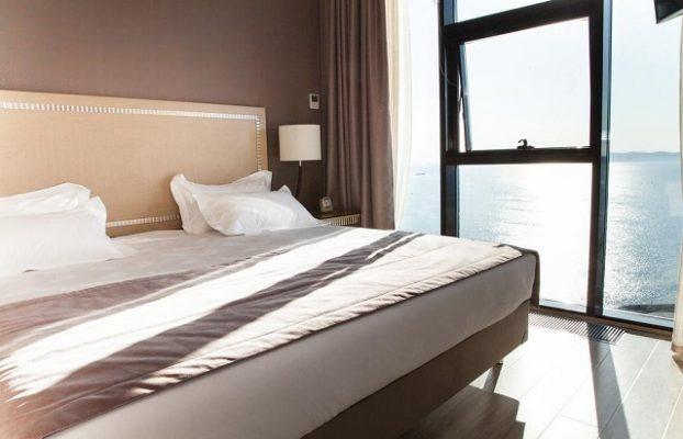 постель у окна в пол с видом на море