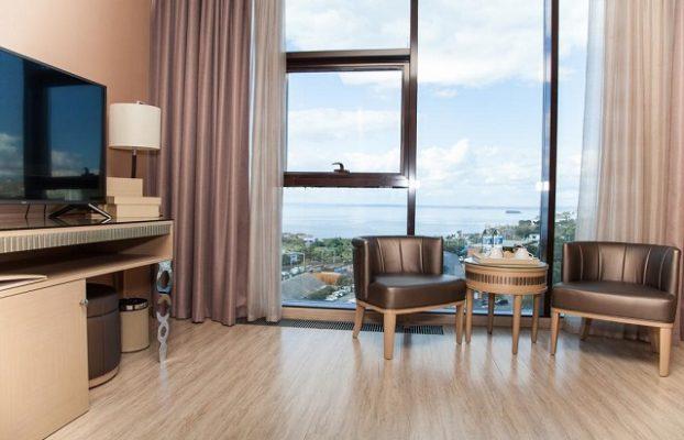 вид на море через окна во всю стену в номере отеля